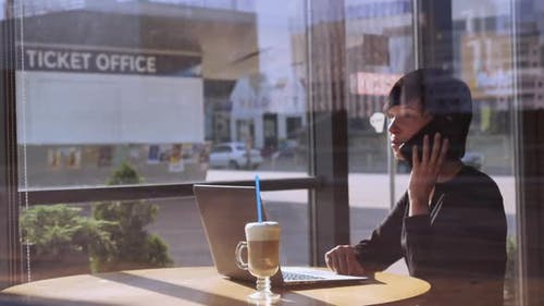 Businesswoman Talking By Mobile in Coffeehouse
