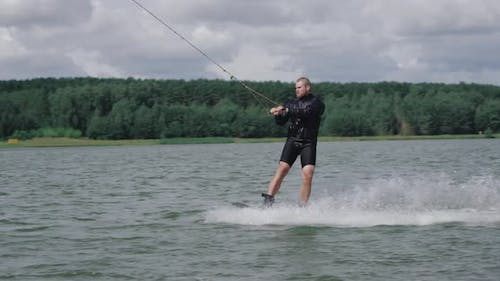 Wakeboarding on the Lake Near Forest, Sportsman Surfs on Water and Does a Somersault, Ride on