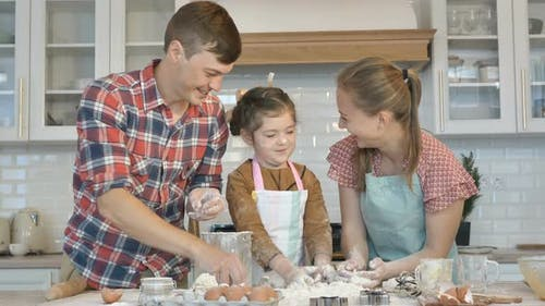 Family with Girl Has Fun Touching Faces By Palms with Flour