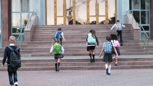Little Pupils in Uniform Run Up Stairs To School on Warm Day