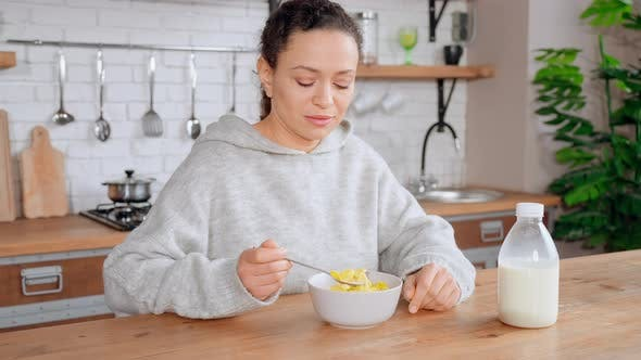 Woman Eating Cereal Flakes with Milk