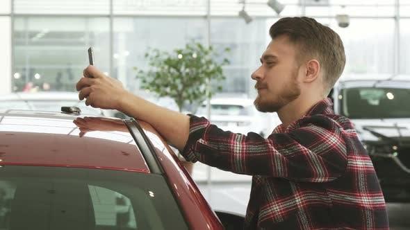 Thumbnail for Cheerful Man Using Smart Phone Showing Car Keys To the Camera Posing at the Dealership