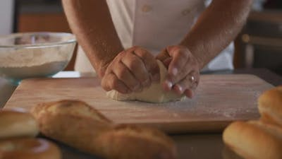 Chef kneading bread dough at bakery