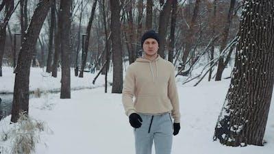 Man in Sportswear Walking in Snow Covered Park