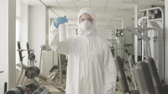 Thumbnail for Middle Shot of Serious Woman in Protective Suit and Respirator Spraying Disinfectant in Gym