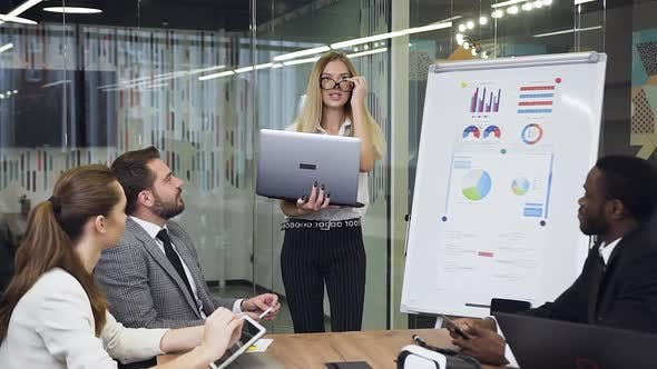 Blond Business Lady Presenting Business Strategy Using flip Chart Board