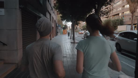 Thumbnail for A Back View of a Couple Jogging Along the Paved Sidewalk