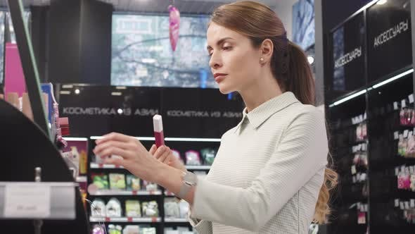 Woman Holding Lipstick Testers In Cosmetics Store