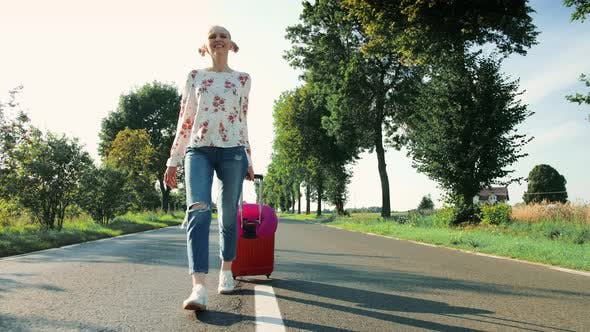 Thumbnail for Cheerful Young Lady with Suitcase Walking on Road.