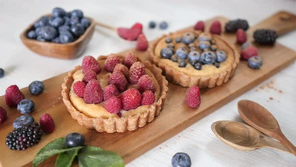 Thumbnail for Vegan Gluten-Free Tartlets With Fresh Berries On Wooden Board On Table.