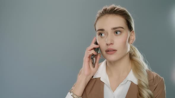 Thumbnail for Annoyed Business Woman Calling Mobile Phone on Gray Background
