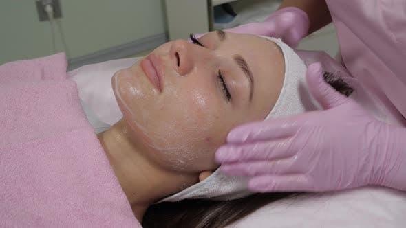 Thumbnail for Die Kosmetikerin trägt ein Peeling Mittel auf die Stirn der Frau