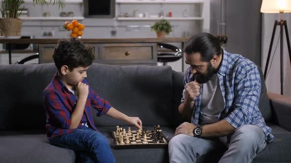 Thumbnail for Clever Son Moving Knight Piece During Chess Game
