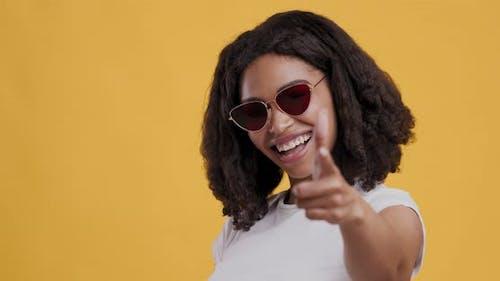 Black Woman in Sunglasses Indicating Happily at Camera