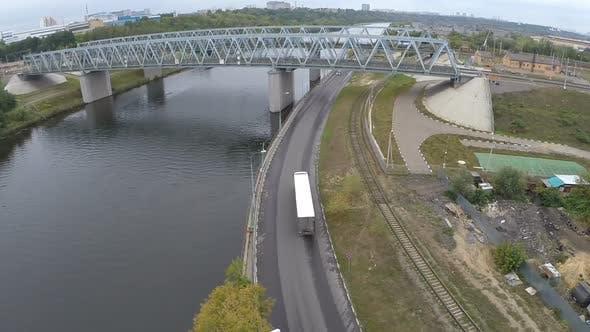 Flying over railway bridge and car traffic