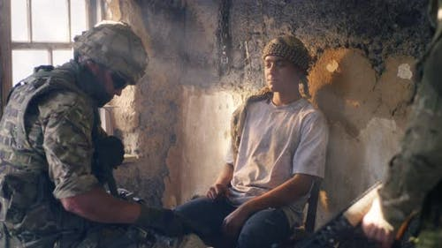 Male Soldier Interrogating Young Prisoners