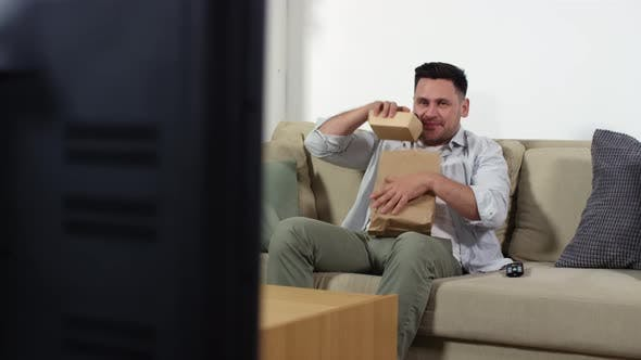 Thumbnail for Cheerful Man Eating Fast Food and Watching TV in Living Room