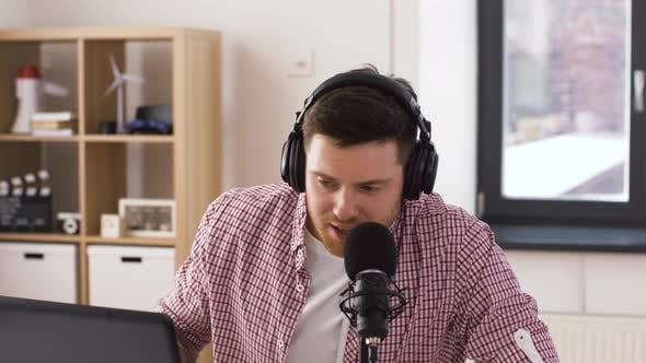 Thumbnail for Man in Headphones with Laptop Speaks To Microphone