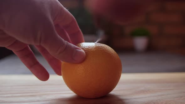 Man's Hands Cutting Fresh Grapefruit on Wooden Desk with Knife. Healthy Lifestyle Concept.