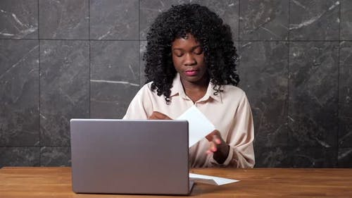 Black Businesswoman Opens Envelope with Letter Shocked