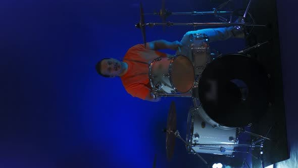 Thumbnail for Vertical Video Bright Neon Light a Male Drummer Plays in a Studio in Neon Light and Smoke