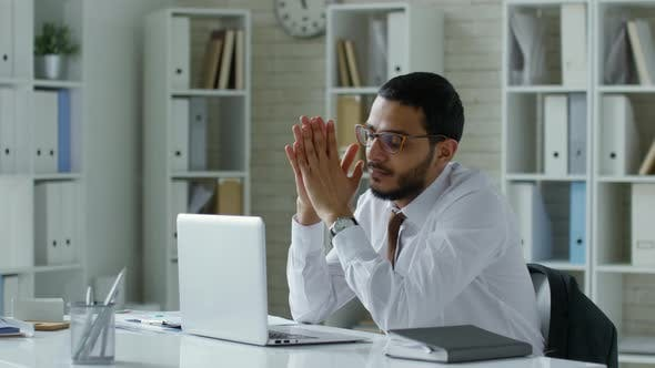 Thumbnail for Middle Eastern Businessman Reading from Laptop Screen at Office Desk
