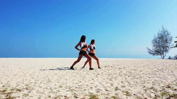 Thumbnail for Young happy ladies on photoshoot in the sun at the beach on clean white sand and blue background 4K