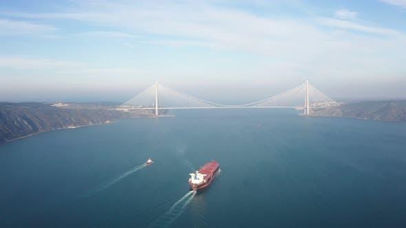 Cargo Ship And Suspension Bridge Aerial View