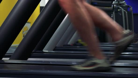 Thumbnail for A Fit Man Jogs on a Treadmill in a Gym - Side Closeup on the Feet
