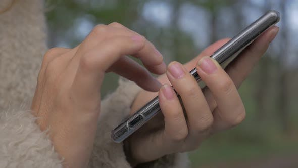 Thumbnail for Woman typing on smart phone  in nature 1920X1080 HD slow motion  footage - Slow motion typing on mob