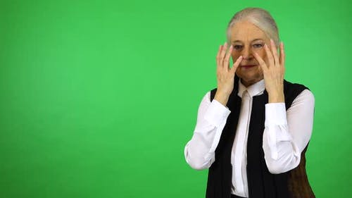 An Elderly Woman Uncovers Her Eyes and Looks Around in Confusion