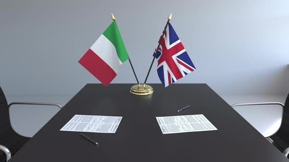 Flags of Italy and the United Kingdom on the Table