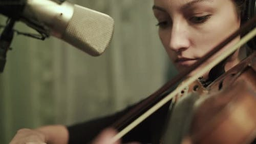 Female Violinist Rehearsing with Headphones at the Microphone