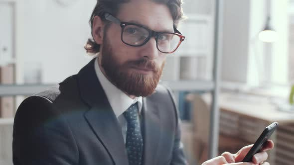 Thumbnail for Young Cheerful Businessman Typing on Smartphone and Smiling at Camera