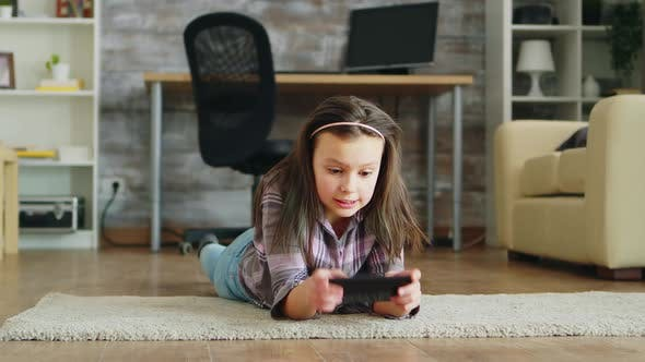 Thumbnail for Cheerful Little Girl Lying Down on the Floor Playing Video Games