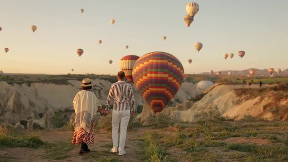Man and Woman Looking at Hot Air Balloons, Couple in love among balloons