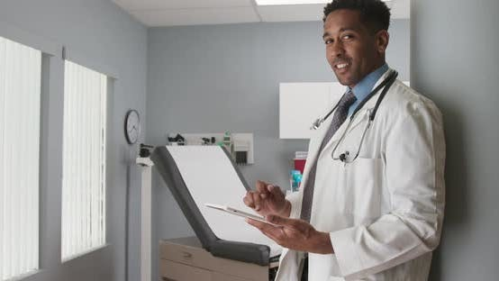 Thumbnail for Charming black medical doctor using tablet computer while smiling at camera