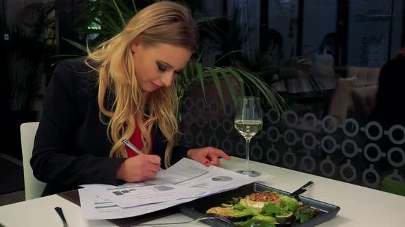 Thumbnail for A Young, Beautiful Woman Sits at a Table in a Restaurant and Writes on a Paper