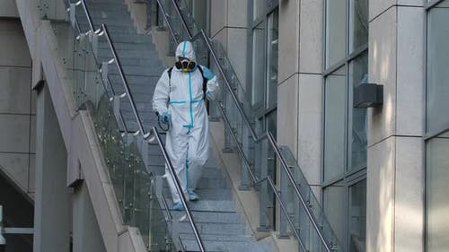 Cleaning City Streets with a Pressure Washer. A Janitor Disinfects Steps and Handrails in a Public