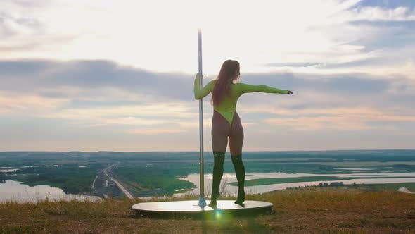 Cover Image for Pole Dance on Nature - Sexy Attractive Woman in Green Swimsuit Dancing By the Pole