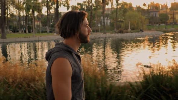 Man Walking Around A Lake