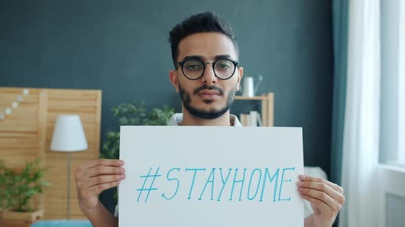 Portrait of Handsome Arab Man Standing at Home with Stayhome Poster During Covid-19 Outbreak