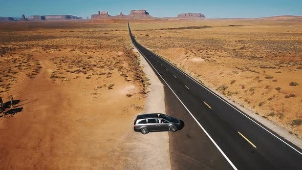 Thumbnail for Drone Follows Silver Minivan Car Taking and Moving Along Iconic American Desert Highway Road