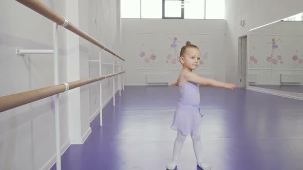 Cute Little Ballerina in Leotard Whirling in Dance at Ballet School