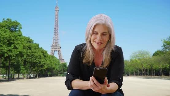 Thumbnail for Elderly white female in Paris near Eiffel Tower checks smartphone