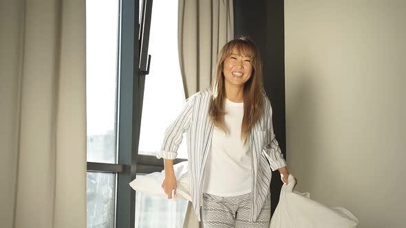 Contented Woman in Pajamas is Having Fun in the Bedroom Jumping on the Bed and Throwing White