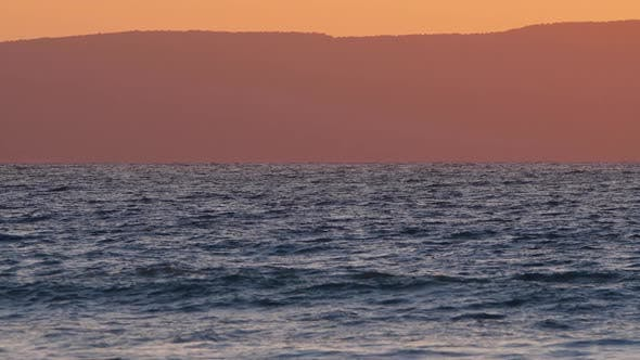 Natural Dramatic Sunrise Seascape with Mountains Sunset Sun Shining Through Waves Ocean and Sea Slow