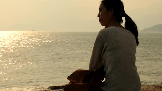 Thumbnail for Woman looking at the sea under sunset