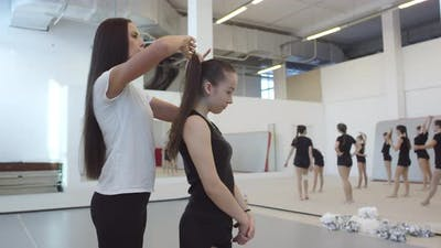 Female Cheer Coach Making Ponytail for Student