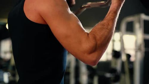 Close-up of Unrecognizable Young Man with Muscular Wiry Body Lifting Barbell.